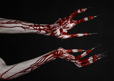 Bloody hand with syringe on the fingers, toes syringes, hand syringes, horrible bloody hand, halloween theme, zombie doctor, black. Background, isolated studio Stock Images