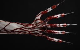 Bloody hand with syringe on the fingers, toes syringes, hand syringes, horrible bloody hand, halloween theme, zombie doctor, black Royalty Free Stock Photo