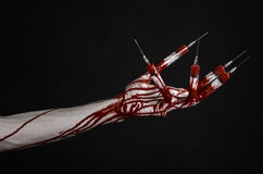 Bloody hand with syringe on the fingers, toes syringes, hand syringes, horrible bloody hand, halloween theme, zombie doctor, black Royalty Free Stock Images