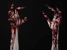 Bloody hand with syringe on the fingers, toes syringes, hand syringes, horrible bloody hand, halloween theme, zombie doctor, black. Background, isolated studio Royalty Free Stock Photos