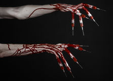 Bloody hand with syringe on the fingers, toes syringes, hand syringes, horrible bloody hand, halloween theme, zombie doctor, black. Background, isolated studio Stock Photography