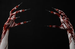 Bloody hand with syringe on the fingers, toes syringes, hand syringes, horrible bloody hand, halloween theme, zombie doctor, black Stock Photos