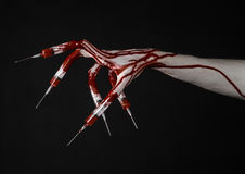 Bloody hand with syringe on the fingers, toes syringes, hand syringes, horrible bloody hand, halloween theme, zombie doctor, black. Background, isolated studio Stock Image