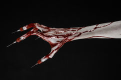 Bloody hand with syringe on the fingers, toes syringes, hand syringes, horrible bloody hand, halloween theme, zombie doctor, black Stock Images