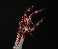 Bloody hand with syringe on the fingers, toes syringes, hand syringes, horrible bloody hand, halloween theme, zombie doctor, black. Background, isolated studio Stock Photos