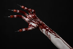 Bloody hand with syringe on the fingers, toes syringes, hand syringes, horrible bloody hand, halloween theme, zombie doctor, black. Background, isolated studio Royalty Free Stock Images