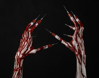 Bloody hand with syringe on the fingers, toes syringes, hand syringes, horrible bloody hand, halloween theme, zombie doctor, black Royalty Free Stock Photos