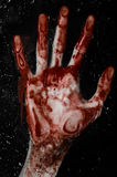 The bloody hand on the wet glass, the bloody window, an imprint of bloody hands, zombie, demon, killer, horror Stock Photo
