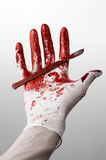 Bloody hands in gloves with the scalpel, white background, isolated, doctor, killer, maniac. Studio Stock Photos
