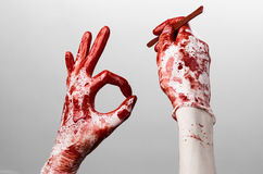 Bloody hands in gloves with the scalpel, white background, isolated, doctor, killer, maniac. Studio Stock Image