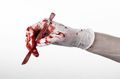 Bloody hands in gloves with the scalpel, white background, isolated, doctor, killer, maniac. Studio Stock Photo