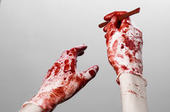 Bloody hands in gloves with the scalpel, white background, isolated, doctor, killer, maniac Royalty Free Stock Photo