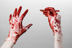 Bloody hands in gloves with the scalpel, white background, isolated, doctor, killer, maniac. Studio Royalty Free Stock Image