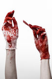 Bloody hands in gloves with the scalpel, white background, isolated, doctor, killer, maniac. Studio Royalty Free Stock Photography