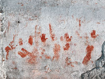 Bloody hands painted on old wall. Red hands and smudges painted on wall looking bloody Royalty Free Stock Photography