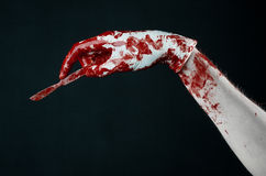 Bloody hands in white gloves, a scalpel, a nail, black background, zombie, demon, maniac Stock Photography