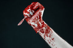 Bloody hands in white gloves, a scalpel, a nail, black background, zombie, demon, maniac Stock Photos