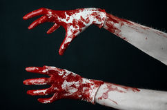 Bloody hands in white gloves, a scalpel, a nail, black background, zombie, demon, maniac. Studio Royalty Free Stock Image