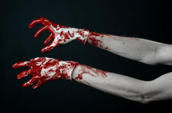 Bloody hands in white gloves, a scalpel, a nail, black background, zombie, demon, maniac. Studio Stock Image