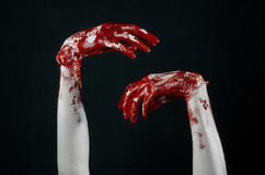 Bloody hands in white gloves, a scalpel, a nail, black background, zombie, demon, maniac. Studio Stock Photo