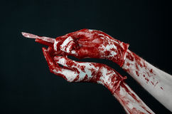 Bloody hands in white gloves, a scalpel, a nail, black background, zombie, demon, maniac. Studio Royalty Free Stock Photos