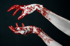 Bloody hands in white gloves, a scalpel, a nail, black background, zombie, demon, maniac. Studio Stock Photos