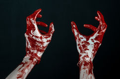 Bloody hands in white gloves, a scalpel, a nail, black background, zombie, demon, maniac. Studio Royalty Free Stock Images