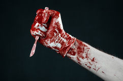 Bloody hands in white gloves, a scalpel, a nail, black background, zombie, demon, maniac. Studio Stock Images