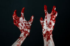 Bloody hands in white gloves, a scalpel, a nail, black background, zombie, demon, maniac. Studio Royalty Free Stock Photography