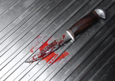 Bloody knife. With wooden handle on a silver sink top stock photo