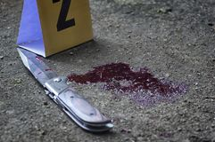Bloody knife and criminal markers on ground, Homicide evidence.Crime scene investigation. royalty free stock image