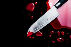 Bloody knife isolated on black stock photography