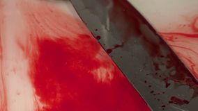 Bloody knife in a sink. Water and mixed blood flow stock video footage