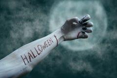 Bloody lettering Halloween on dead arm.