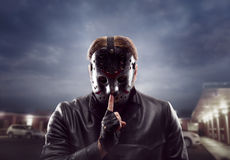 Bloody maniac in hockey mask show do not talk sign Stock Image