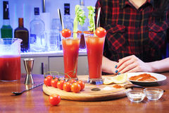 Bloody Mary and barman. Decorated bloody Mary with celery and tomato. Alcoholic cocktail, drinks on a wooden board. Called Bloody Mary. Good cocktail booze with Stock Photos