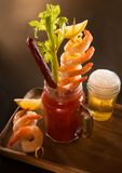 Bloody Mary drink with shrimp and beer chaser. Bloody Mary cocktail in a mason jar mug with shrimp, celery, beef stick, lemon wedge with a beer chaser on a wood royalty free stock images