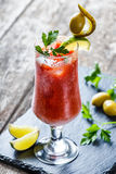 Bloody Mary cocktails with tomato juice and spicy vodka, decorated with pickle and olive garnish. On stone slate background on rustic table. Summer drinks and Royalty Free Stock Photo