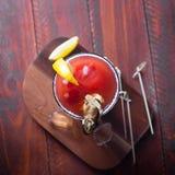 Bloody Mary del cóctel con hielo, sal y bocados en vidrio en una tabla de madera Endecha plana fotografía de archivo libre de regalías