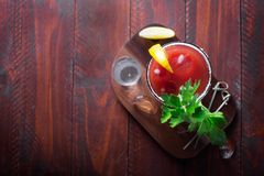 Bloody Mary del cóctel con hielo, sal y bocados en vidrio en una tabla de madera fotografía de archivo