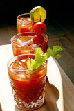 Bloody Mary Trio. Bloody marys with celery, lime and tomato garnishments Royalty Free Stock Images