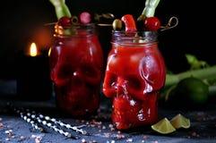 Bloody Marycoctailen i exponeringsglas-skalle med selleripinnar, rosa färger saltar, limefrukt och canapes från på burk grönsaker royaltyfria bilder
