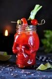 Bloody Marycoctailen i exponeringsglas-skalle med selleripinnar, rosa färger saltar, limefrukt och canapes från på burk grönsaker royaltyfri bild