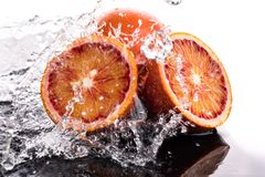 Bloody orange whole and halves, slices with reflection on white and black background in a spray of water.  royalty free stock images