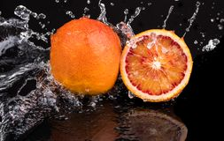 Bloody orange whole and halves, slices with reflection on white and black background in a spray of water.  stock images