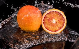 Bloody orange whole and halves, slices with reflection on white and black background in a spray of water.  royalty free stock image