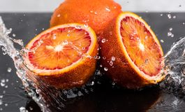 Bloody orange whole and halves, slices with reflection on white and black background in a spray of water.  stock image