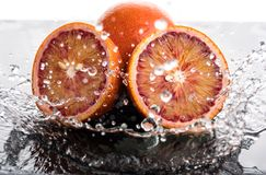 Bloody orange whole and halves, slices with reflection on white and black background in a spray of water.  royalty free stock photography