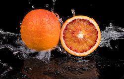 Bloody orange whole and halves, slices with reflection on white and black background in a spray of water.  royalty free stock photo