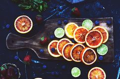 Bloody oranges and limes on dark background Stock Images